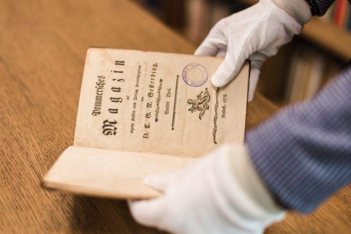 Osoba w białych rękawiczkach prezentuje zabytkową książkę