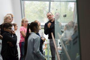 Mężczyzna w okularach i czarnym swetrze mówi do grupy dzieci stojącej na schodach