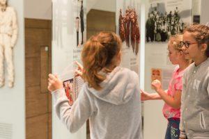 Grupa kolorowo ubranych dziewczynek ogląda ryciny na szkalnych panelach