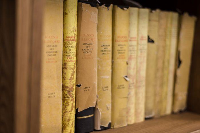 Stare książki w języku łacińskim w zniszczonych obwolutach ustawione na półce