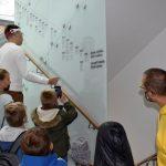 Dwóch mężczyzn - jeden w żółtej bluzie i drugi w białym swetrze oraz grupka dzieci ogląda teksty na ścianie klatki schodowej