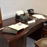 Zabytkowe biurko a na nim liczydło, ksiązki, papiey, okulary i maszyna do pisania
