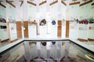 Wystawa kolorowych zdjęć na szklanych podłużnych panelach. Na pierwszym planie szyba, w której odbijają się panele