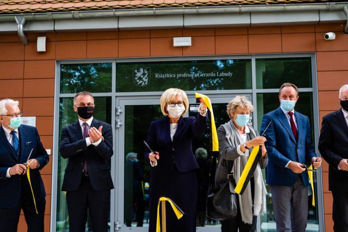 Grupa osób w maseczkach stoi przed budynkiem z czerownej cegły. Kobieta w środku pokazuje żółto-czarną wstążkę