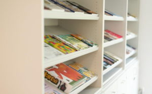 Kolorowe ksiązki i broszury ułożone na skośnie ustawionych białych półkach