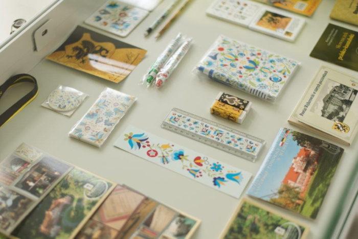 w jasnej gablocie ułożone pocztówki i gadżety z kolorowymi motywami