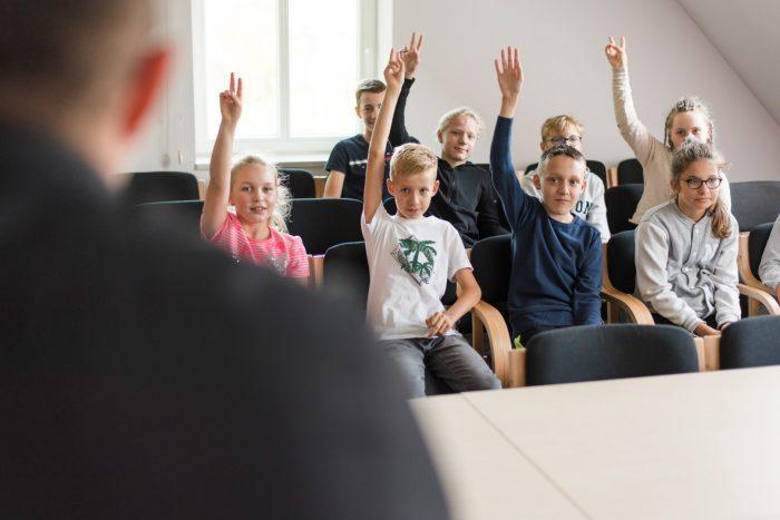 Dzieci siedzą na krzesłach i podnoszą ręce do góry