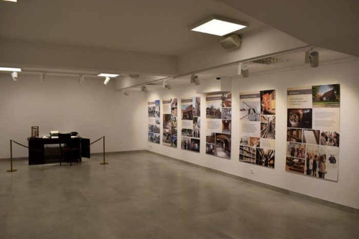 W nowoczesnej sali z białymi ścianami stoi stare biurko z eksponatami, na ścianach wiszą fotografie