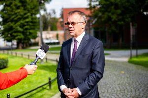 Mężczyzna w ciemnych okularach, ubrany w granatowym garnitur i fioletowy krawat przemawia do mikrofonu