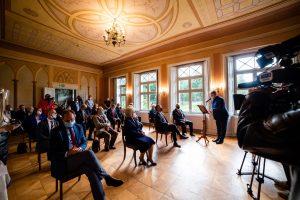 Grupa elegancko ubranych osób siedzi w zabytkowym pomieszczeniu. Jeden mężczyzna przemawia przy mikrofonie. Po lewej stronie kamera telewizyjna.sw
