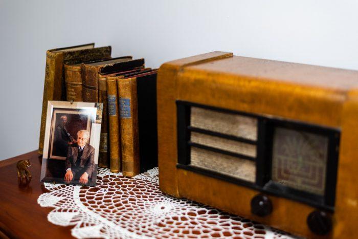 Zabytkowe radio i książki oraz zdjęcie w ramce stoją na koronkowej białej serwetce rozpostartej na drewnianej półce